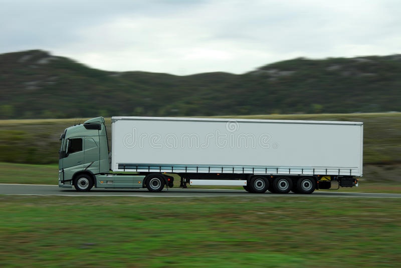 Green lorry with white trailer drive fast royalty free stock photo