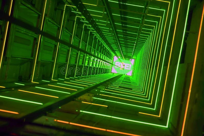 Green Luminous Lift Tunnel. Elevator corridor in the building lit by green elumination. Futuristic elevator shaft is located in a high tower. Lift shaft in a royalty free stock photos