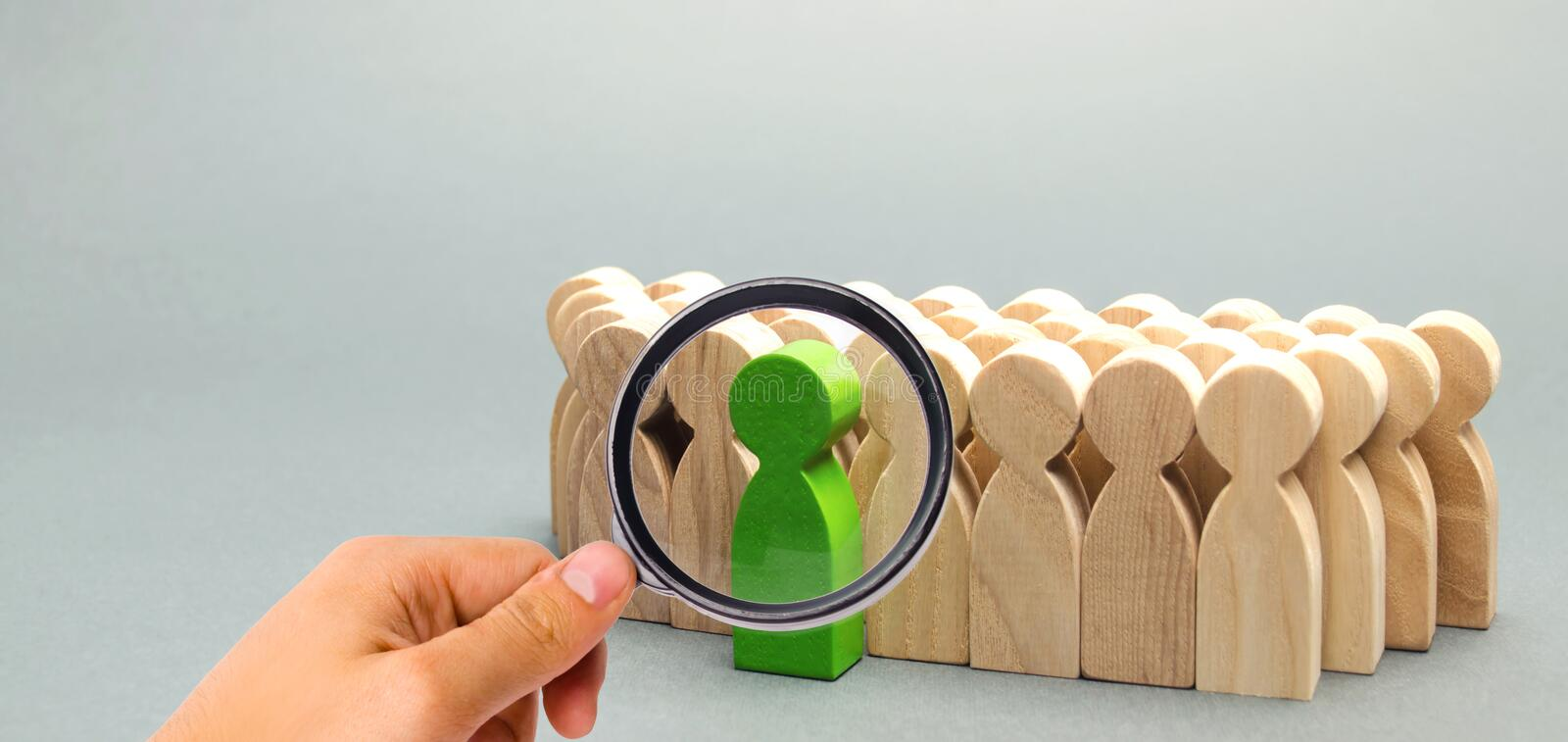 Green man coming out of the crowd. The chosen person among others. A talented worker. Promotion. Concept of search for a worker. royalty free stock photography