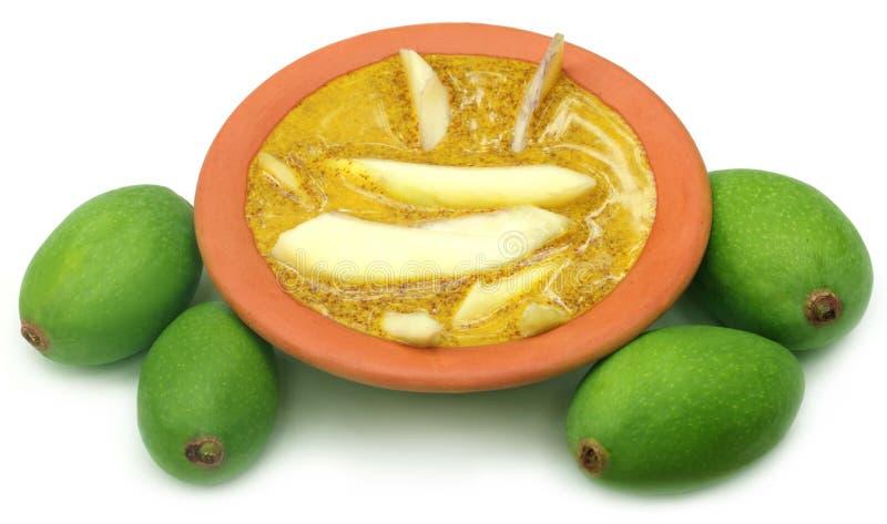 Green mango with kasundi. – A Bengali relish over white background royalty free stock image
