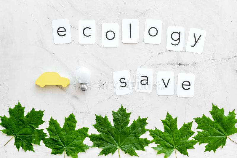 Green maple leaves, car figure, bulb and ecology save text for eco concept on marble background top view. Eco friendly. Green maple leaves, car figure, bulb and stock photos