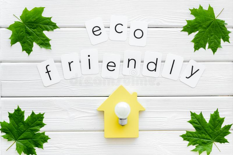Green maple leaves, house figure and bulb and eco friendly text for ecology concept on white wooden background top view. Save planet. Green maple leaves, house royalty free stock images