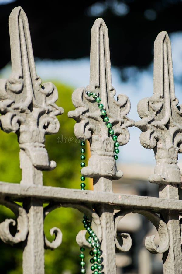 Green Mardi Gras Beads on Fleur de Lis Fencing-New Orleans, Louisiana. Green Mardi Gras Beads on gray wrought iron Fleur de Lis Fencing - Garden District - New stock photos