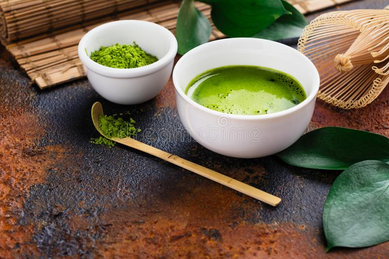 Green matcha tea drink and tea accessories on dark rusty background royalty free stock photos