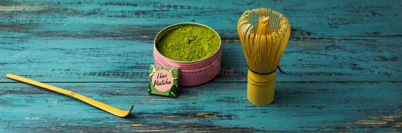 Green matcha tea powder and tea accessories on blue wooden background. Japanese tea ceremony concept stock photo