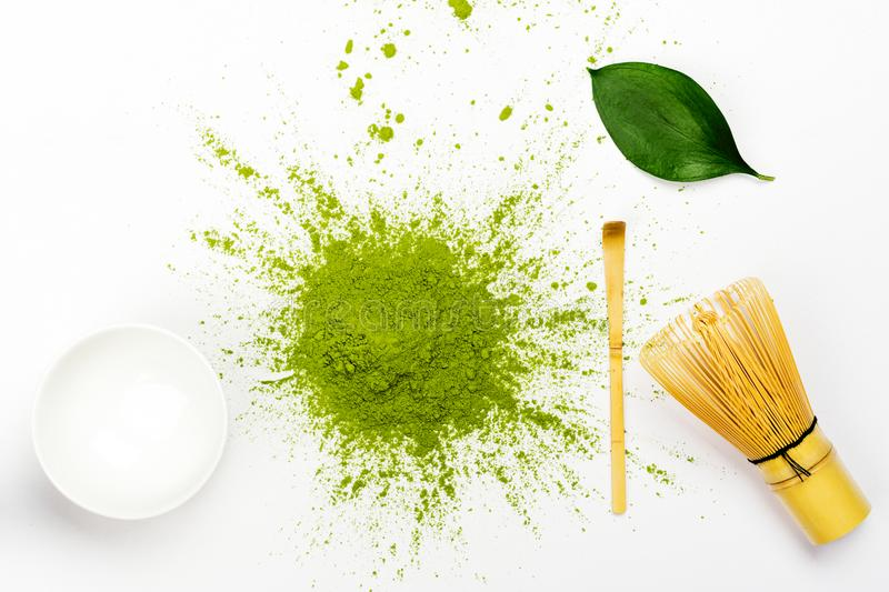Green matcha tea powder and tea accessories on white background royalty free stock photography
