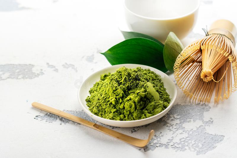 Green matcha tea powder and tea accessories on white background stock images