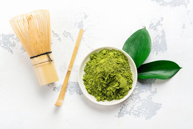 Green matcha tea powder and tea accessories on white background royalty free stock image