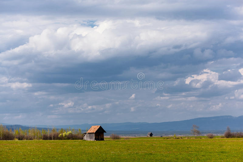 Green meadow and chalets. Plain in the foothills with a small chalets in Transylvania, Romania. Upstairs, a beautiful, picturesque sky with clouds stock photography