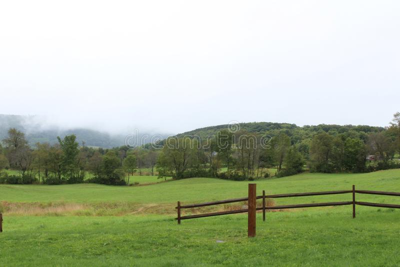 Green meadow with fence opening and foggy mountain scene behind stock photo