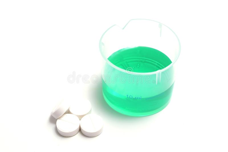 Green medical liquid in a plastic cup with pills stock images