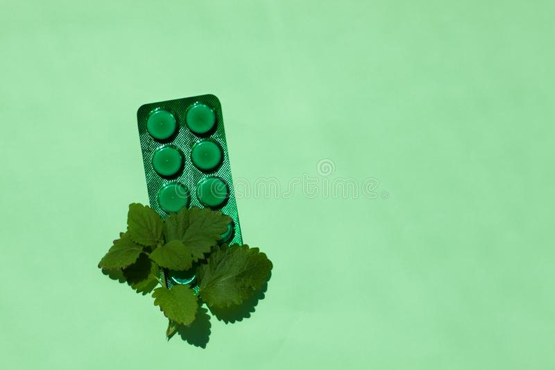 A green medical tablets plate with mint leaves, a remedy against allergy and runny nose, colds, viral diseases royalty free stock photos
