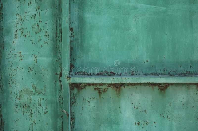 Green metal dirty sheet fence. Rust grunge leaks template blank. Old paint on the fence. Copper abstract wall art stock photography
