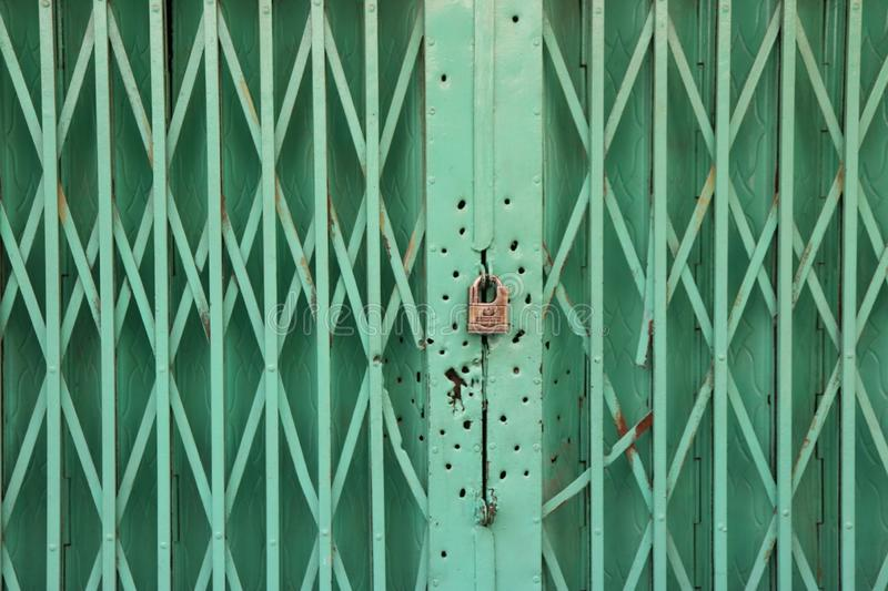 Green metal door with look and bullet holes around it stock photos