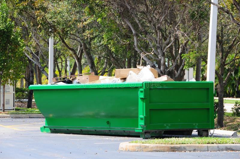 Green metal dumpster, South Florida. Green painted steel dumpster filled with cardboard boxes and other trash in a parking lot in Florida stock photography