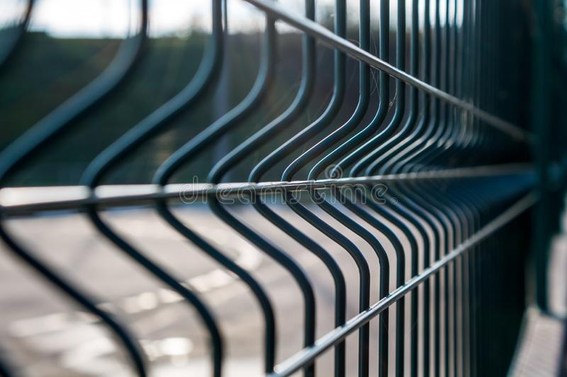 Green metal fence. Symmetrical arrangement of branches stock image