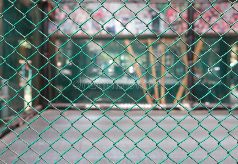 Green metal grille fence against blur of boxing stage stock photography