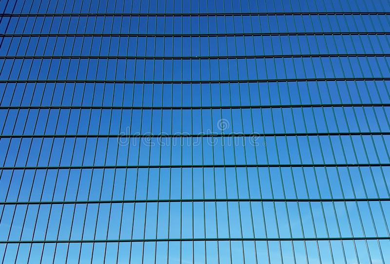 Green metal mesh fence with square cells against a blue sky. Background of parallel lines arranged in perspective in an inclined stock image