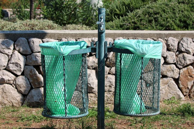 Green metal pole with dual outdoor public trash cans with fresh new nylon bags inserted and broken ashtray on top with traditional. Stone wall and garden royalty free stock photos