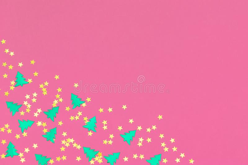 Green christmas trees and gold stars confetti sparse on pink background. Green metallic foil christmas trees and gold stars confetti sparse on pink background royalty free stock photo