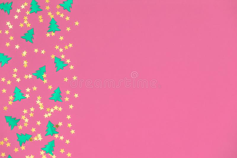 Green christmas trees and gold stars confetti sparse on pink background. Green metallic foil christmas trees and gold stars confetti sparse on pink background stock photography