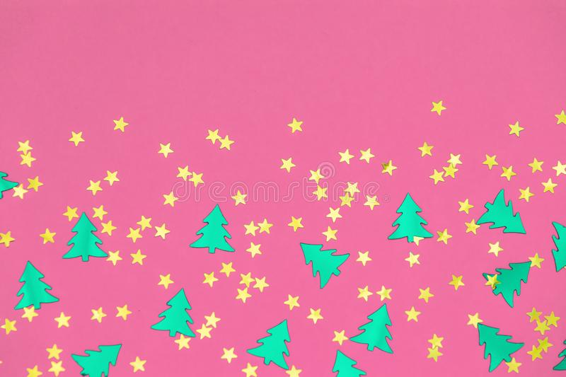 Green christmas trees and gold stars confetti sparse on pink background. Green metallic foil christmas trees and gold stars confetti sparse on pink background royalty free stock image