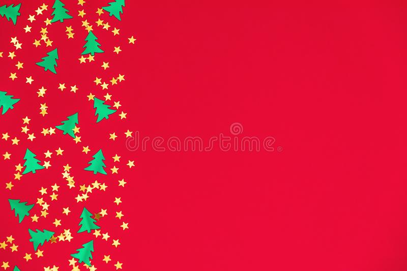Green christmas trees and gold stars confetti sparse on red background. Green metallic foil christmas trees and gold stars confetti sparse on red background vector illustration