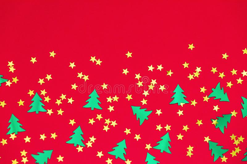 Green christmas trees and gold stars confetti sparse on red background. Green metallic foil christmas trees and gold stars confetti sparse on red background royalty free stock photo