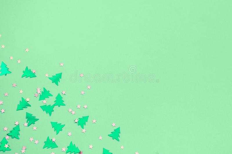 Green metallic foil christmas trees and stars confetti sparse on trendy neo mint colored background. Green metallic foil christmas trees and stars confetti vector illustration