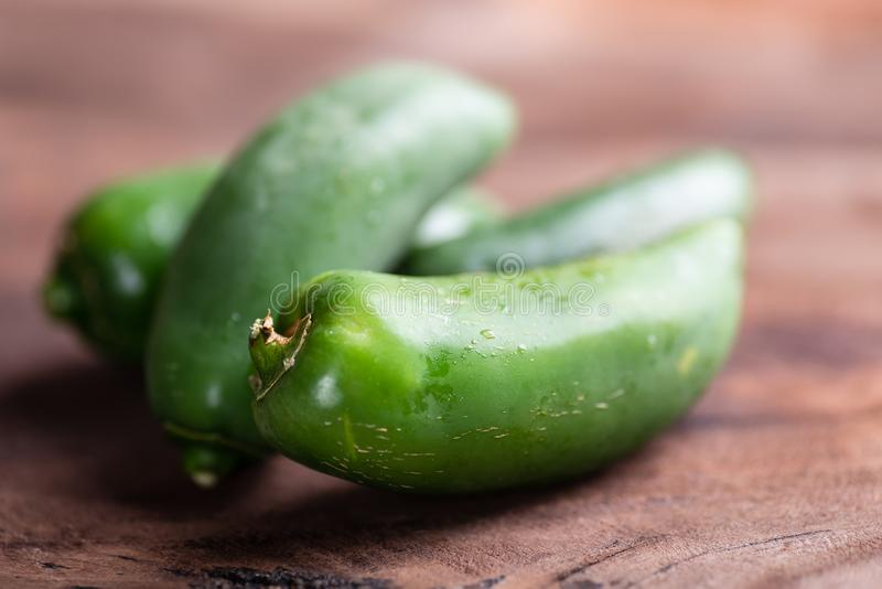Green Mexican Jalapeno chili on wooden background. Fresh vegetables for cooking royalty free stock photos
