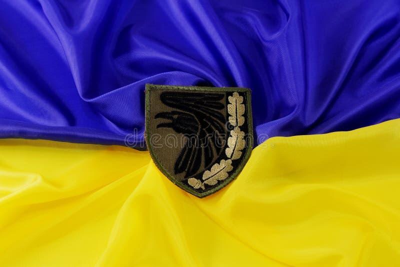 Green military chevron of the Ukrainian army, on the yellow-blue state flag of Ukraine. February 12, 2019, Kiev, Ukraine. Illustrative editorial royalty free stock photography