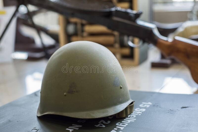Green military helmets, stand in the arms store on the background of machine guns and machine guns. Weapon counter, souvenir decorative military accessories stock photography