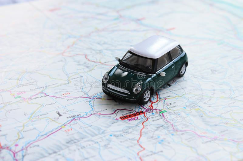 Green miniature car on paper map stock photography