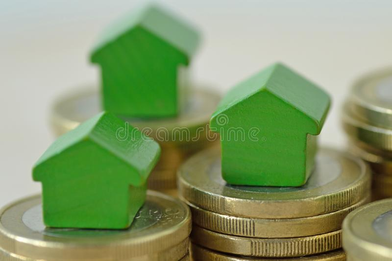 Green miniature houses on coin stacks - Concept of real estate investment, mortgage, home insurance and loan, eco-friendly house stock photo