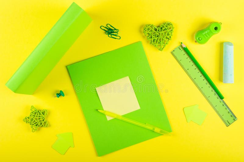 Green Mock up exercise book and textbook for school subjects and stationery on a yellow background. royalty free stock image