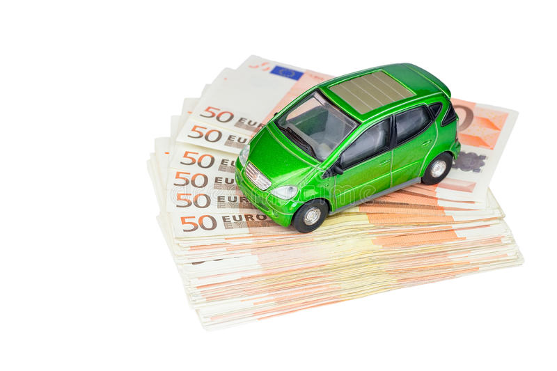 Green model car on pile of euro bills. Green model car on stack of euro notes isolated on white background royalty free stock image