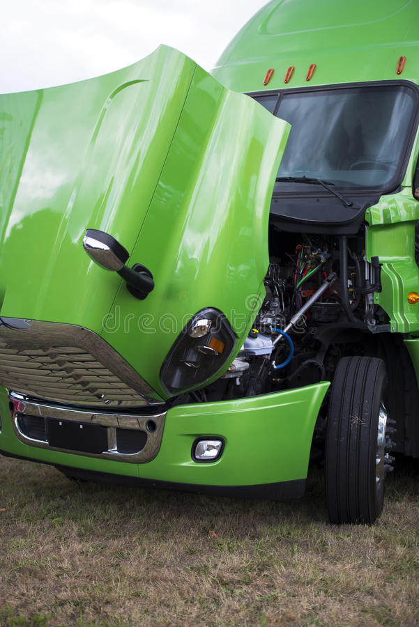 Green modern semi truck with open hood and engine. Huge professional bright shiny clean green big rig semi truck with an open hood to check the performance of royalty free stock images
