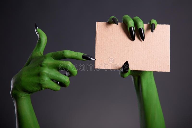 Green monster hand with black nails pointing on blank piece of c. Ardboard, Halloween theme stock photography