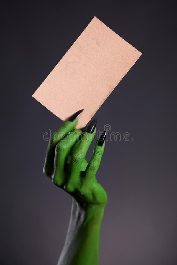 Green monster hand holding blank piece of cardboard. Horror Halloween theme royalty free stock photo