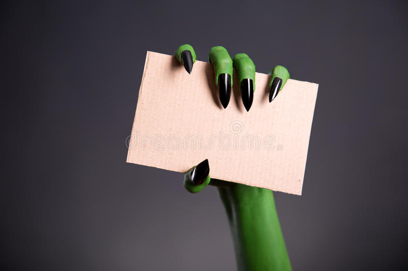 Green monster hand with sharp nails holding blank piece of cardboard. Halloween theme stock photos