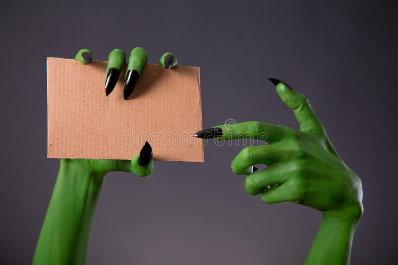 Green monster hands with black long nails pointing on blank piec. E of cardboard, Halloween theme stock photography