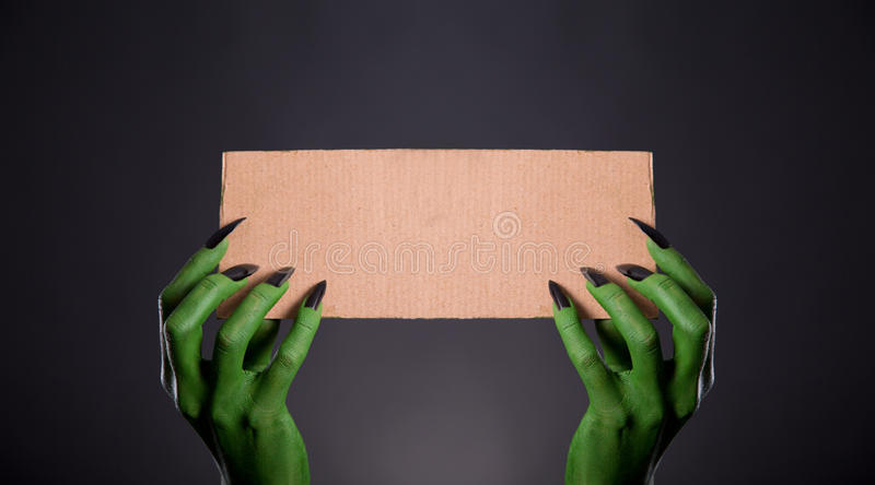 Green monster hands with black nails holding empty piece of card. Board, Halloween theme royalty free stock photography