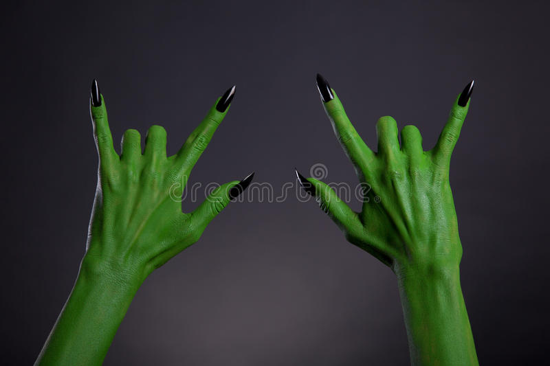 Green monster hands with black nails showing heavy metal gesture. Halloween theme stock photos