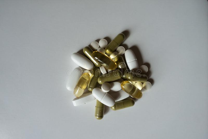 Green moringa and yellow fish oil capsules, white calcium caplets and vitamin K2 tablets. From above stock image