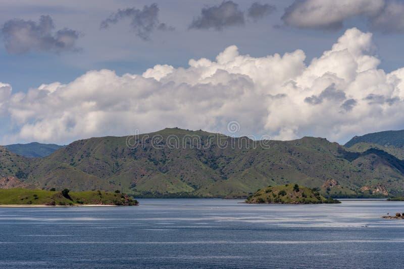 Green mountain range and islets on Komodo Island bay, Indonesia. Komodo Island, Indonesia - February 24, 2019: Green mountain range descending on sand beach stock image