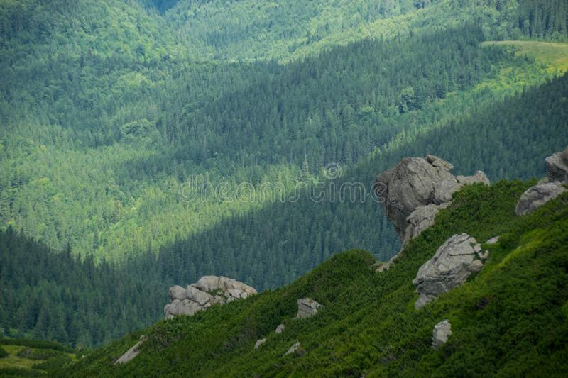 Green mountain valley and rocks. Top-down view to the green mountain valley and Massive boulders on a green mountainside. Hiking path in Carpathian National royalty free stock photo