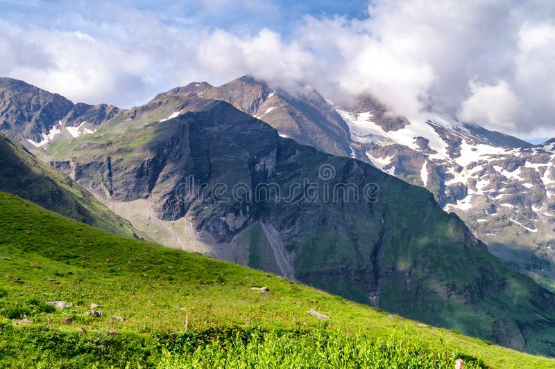 Green mountain valley and snowy mountainsides in the clouds, Austria. Green mountain valley and snowy mountainsides in the clouds. Austrian Alps royalty free stock image
