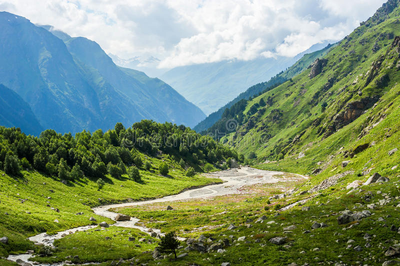 Green mountain valley in summer russian Caucasus mountains. Beautiful green mountain valley with a small rough stream illuminated by the sun. Summer russian royalty free stock images