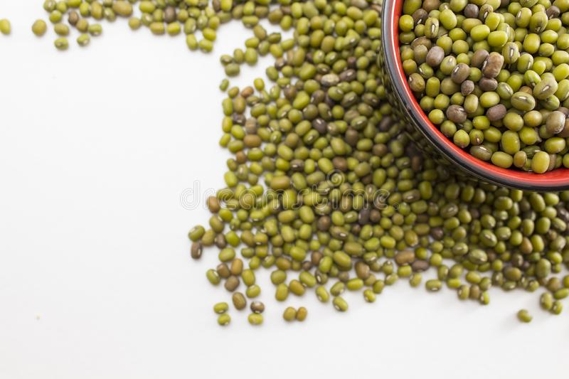 Green mung beans in a bowl. Green mung beans in the bowl and around. Background. Close up stock photography