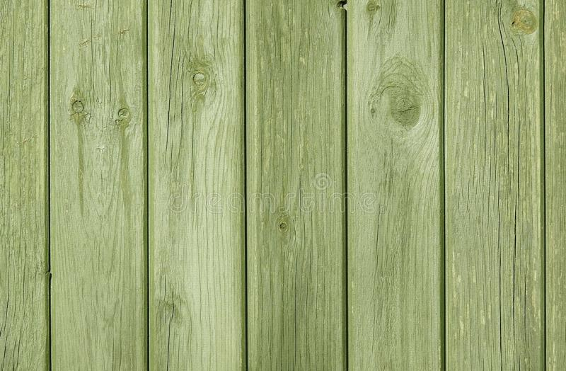 Green Natural Wood Plank Fence With Visible Grain Background/ Backdrop. A green fence made of timber painted green. Natural wood, visible grain stock photography